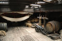 Pirate ship hold. Below deck on a replica, tourist, pirate ship.  A small , ropes, hammock, wine barrel are in view Royalty Free Stock Image