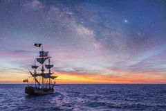 Pirate Ship. Leaving the harbor at the milky way sunset for a long campaign against the loyal marines on the oceans Royalty Free Stock Photo