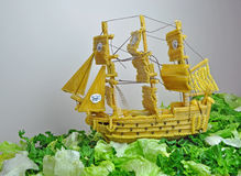 Pirate ship made from pasta. This is a pirate ship made from pasta, sailing on a bed of ice-burg lettuce, it took 3 weeks to make, started with cardboard frame stock images