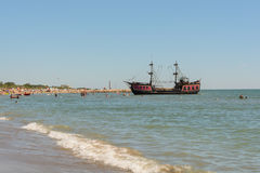 Pirate ship near the beach and bathers Stock Photos
