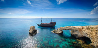 Pirate ship by rock arch,cyprus. Pirate ship sailing past a rock arch in ayia napa,cyprus Stock Photo