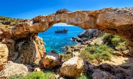 Pirate ship through rock arch,cyprus. A pirate ship seen through a natural rock arch in the cape greco area of eastern cyprus Stock Image
