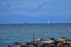 Pirate Ship and Sail Boat off in the distance with rocks in foreground from beach in Puerto Vallarta Mexico. Pirate Ship and Sail Boat off in the distance with Royalty Free Stock Image