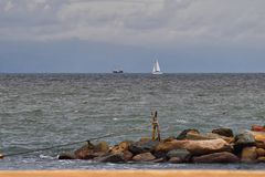 Pirate Ship and Sail Boat off in the distance with rocks in foreground from beach in Puerto Vallarta Mexico. Pirate Ship and Sail Boat off in the distance with Stock Images