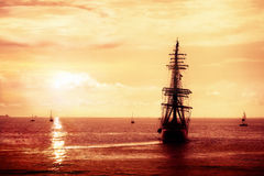 Pirate ship sailing. Treasure seeker, sailing ghost ship on the high seas at dusk. Flying Dutchman in the red sunset Royalty Free Stock Photography