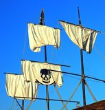 Pirate Ship Sails. Sails of a pirate ship - three are blank, one has a blank skull print - against a cloudless blue sky Royalty Free Stock Photography