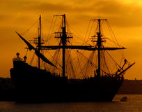 Pirate Ship Sunrise. Silhouette of a Pirate Ship anchored at port in front of a beautiful sunrise Royalty Free Stock Photo