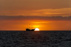 Pirate Ship Sunset. Is sailing at sea silhouetted against a setting sun and a colorful cloudy filled sky Stock Image