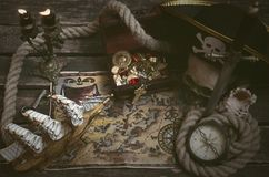 Treasure chest. Pirate ship, treasure map, treasure chest full of gold and a compass on a wooden captain table background stock photography