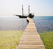 Pirate ship under Jolly Roger Stock Images