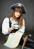 Pirate sitting with a map and magnifying glass Stock Photography