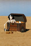 Pirate Skeleton. A pirate skeleton in a treasure chest on a sandy beach royalty free stock image