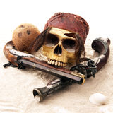 Pirate Skull at the beach. Tropical Pirate scene with a skull, seashells and guns Stock Photography
