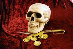 Pirate skull and booty. Pirate Skull with eye sockets and teeth with gold and other booty Royalty Free Stock Image