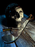 Pirate skull. Dagger and sabre on vintage wooden table stock illustration