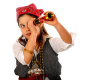 Pirate Spying. An elementary girl dressed as a pirate, peering through a spyglass.  Isolated on white Stock Image