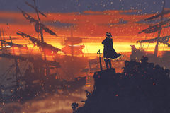 Pirate standing on treasure pile against ruined ships at sunset Stock Photos