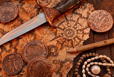 Pirate still life with dagger and map. Pirate still life with decorated dagger, map, ancient coins and pearl necklace on wooden background in candle light stock image