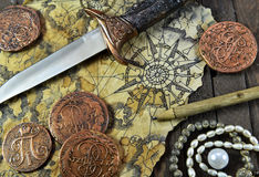 Pirate still life with map, coins and small sword. Pirate still life with decorated dagger, map, ancient coins and pearl necklace on wooden background royalty free stock photo