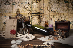 Pirate still life. Pirate objects, pirates booty, pirate still life, chest with a antique jewelry, knot letter with sealing wax on the wooden table, rum in the Royalty Free Stock Image