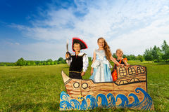Pirate with sword and two princesses stand on ship. Kids play pirate with sword and two princesses stand together on the carton ship and smile Royalty Free Stock Images