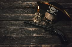 Pirate table. Pirate captain table with pirate hat, human skull, musket and burning candle. Treasure hunter concept background royalty free stock photo