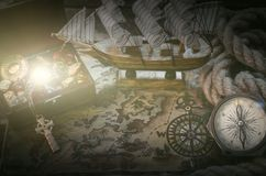 Pirate treasure chest. Pirate ship, treasure map, rope, treasure chest full of gold and a compass on a wooden table background royalty free stock photos