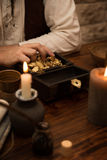 Pirate with a treasure of gold, medieval table with candles, qui Stock Photography