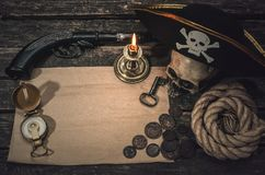 Pirate treasure map. Pirate treasure map with copy space, pirate captain hat, compass, coins, human skull, mooring rope, musket and burning candle. Treasure stock photo