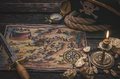 Treasure map. Pirate treasure map, gold nuggets, dagger and pirate hat on aged wooden table background. Sea travel stock images