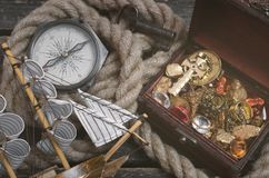 Pirate treasure map. Pirate ship, treasure map, treasure chest full of gold and a compass on a wooden table background royalty free stock photo