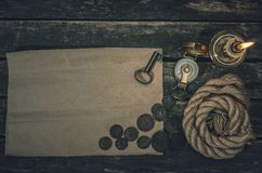 Pirate treasure map. Pirate treasure map with copy space, compass, key from treasure map, mooring rope, and burning candle on wooden table background. Treasure stock images