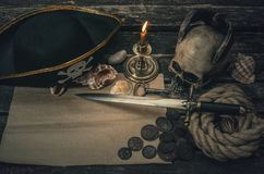 Pirate treasure map. Pirate treasure map with copy space, pirate captain hat, coins, human skull, mooring rope, dagger and burning candle. Treasure hunter royalty free stock photography