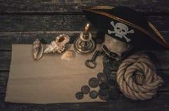 Pirate treasure map. Pirate treasure map with copy space, pirate captain hat, coins, human skull, seashells, mooring rope and burning candle. Treasure hunter stock photo