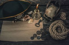 Pirate treasure map. Pirate treasure map with copy space, pirate captain hat, coins, human skull, seashells, mooring rope and burning candle. Treasure hunter stock image