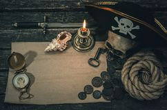 Pirate treasure map. Pirate treasure map with copy space, pirate captain hat, compass, coins, human skull, mooring rope, dagger and burning candle. Treasure stock images