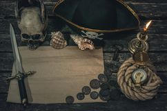 Pirate treasure map. Pirate treasure map with copy space, pirate captain hat, compass, coins, human skull, mooring rope, dagger and burning candle. Treasure royalty free stock photos