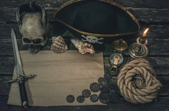 Pirate treasure map. Pirate treasure map with copy space, pirate captain hat, compass, coins, human skull, mooring rope, dagger and burning candle. Treasure stock photography