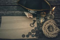 Pirate treasure map. Pirate treasure map with copy space, pirate captain hat, compass, coins, seashell, mooring rope and burning candle. Treasure hunter concept stock images