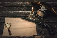 Pirate treasure map. Pirate treasure map with copy space, pirate captain hat, human skull, musket, dagger and burning candle. Treasure hunter concept background royalty free stock images