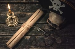 Pirate treasure map. Pirate treasure map scroll, pirate captain hat, human skull, ancient coins and burning candle. Treasure hunter concept background royalty free stock photo