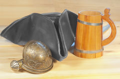 Pirate triangle hat and saber on  wooden background Royalty Free Stock Photography