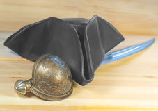 Pirate triangle hat and saber on  wooden background Stock Photo