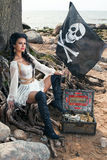 Pirate woman sitting near treasure chest. Beautiful pirate woman sitting near treasure chest on the beach with a bottle of rum and classic pistol in her hands Stock Photo