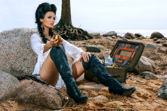 Pirate woman sitting near treasure chest. Beautiful pirate woman sitting near treasure chest on the beach with a golden goblet in her hand Royalty Free Stock Photography