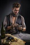 Piraten-Mann mit dem Handy, der durch Tabelle sitzt stockfotografie