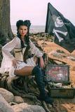 Piratenfrau, die nahe Schatztruhe sitzt Stockfotografie