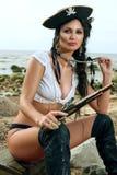 Piratenfrau, die nahe Schatztruhe sitzt Lizenzfreie Stockfotos