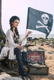 Piratenfrau, die nahe Schatztruhe sitzt Stockbilder