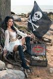 Piratenfrau, die nahe Schatztruhe sitzt Stockfoto